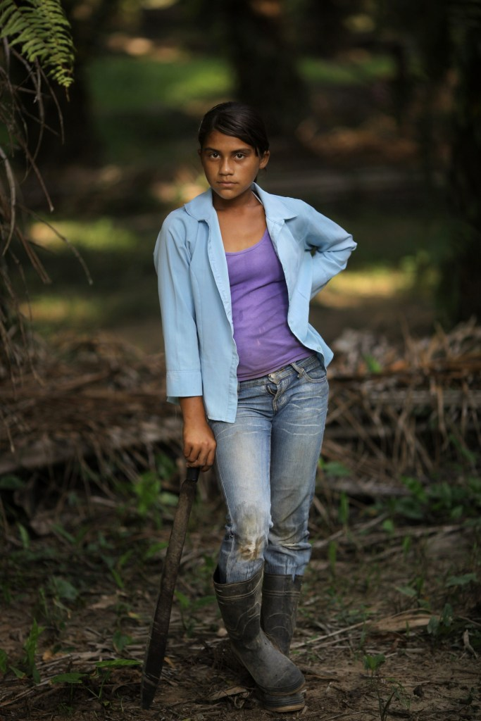 "In this May 7, 2012 photo, Elsia Acosta, 13, takes a break from cutting grass or ""chapeando"" the floors of african palm trees in ""La Confianza"" peasant model city, Bajo Aguan, Honduras. Peasants from MUCA (Movimiento Unificado Campesino del Bajo Aguan) occupied around 7000 sq meters of productive land close to the city of Tocoa in the Valley of Bajo Aguan, eastern coast of Honduras in December, 2009. They operate a comercial production of african palm and they also stablished what they call a ""peasant model city"" called ""La Confianza"" where more than 300 hundred families live. Since then an open conflict between them and the alleged owner of the land, Miguel Facussé, one of the most powerful businessmen in Honduras has left more than 60 people dead including peasants, security guards, a journalist and members of the Honduran national police. (AP Photo/Rodrigo Abd)"