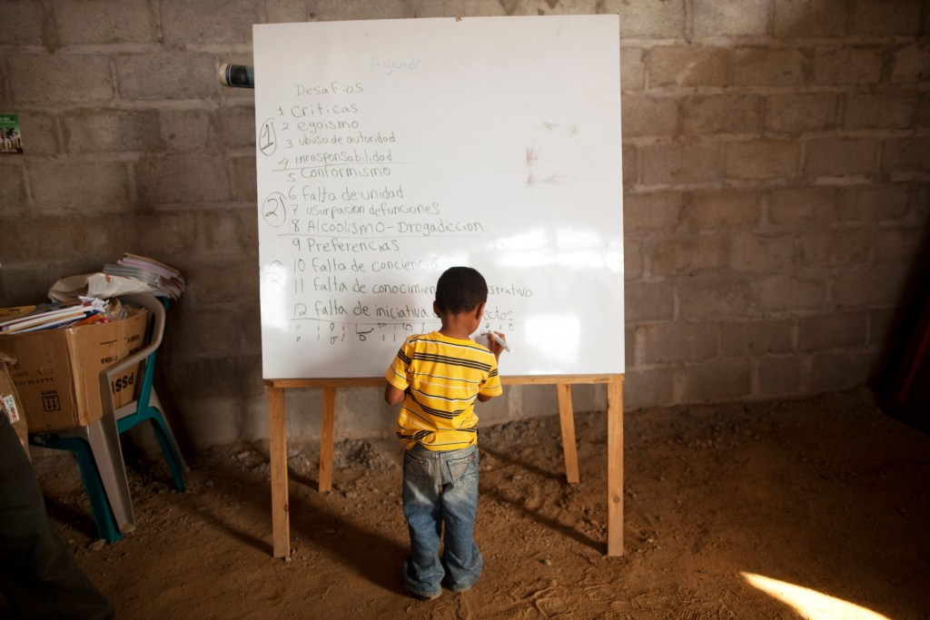 "In this May 5, 2012 photo, a boy draws in a blackboard during a class of political formation for the villagers in ""La Confianza"" peasant model city, Bajo Aguan, Honduras. Peasants from MUCA (Movimiento Unificado Campesino del Bajo Aguan) occupied around 7000 sq meters of productive land close to the city of Tocoa in the Valley of Bajo Aguan, eastern coast of Honduras in December, 2009. They operate a comercial production of african palm and they also stablished what they call a ""peasant model city"" called ""La Confianza"" where more than 300 hundred families live. Since then an open conflict between them and the alleged owner of the land, Miguel Facussé, one of the most powerful businessmen in Honduras has left more than 60 people dead including peasants, security guards, a journalist and members of the Honduran national police. (AP Photo/Rodrigo Abd)"