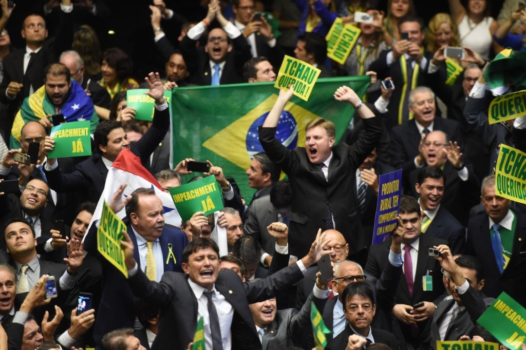 Brazil's lawmakers celebrate after they reached the votes needed to authorize President Dilma Rousseff's impeachment to go ahead, at the Congress in Brasilia on April 17, 2016. Brazilian lawmakers on Sunday reached the two thirds majority necessary to authorize impeachment proceedings against President Dilma Rousseff. The lower house vote sends Rousseff's case to the Senate, which can vote to open a trial. A two thirds majority in the upper house would eject her from office. Rousseff, whose approval rating has plunged to a dismal 10 percent, faces charges of embellishing public accounts to mask the budget deficit during her 2014 reelection. / AFP PHOTO / EVARISTO SA