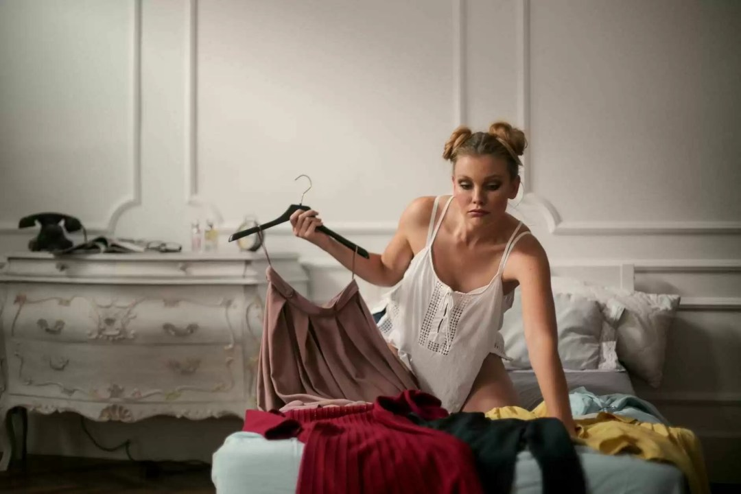 pensive young woman choosing outfit while dressing in light vintage bedroom