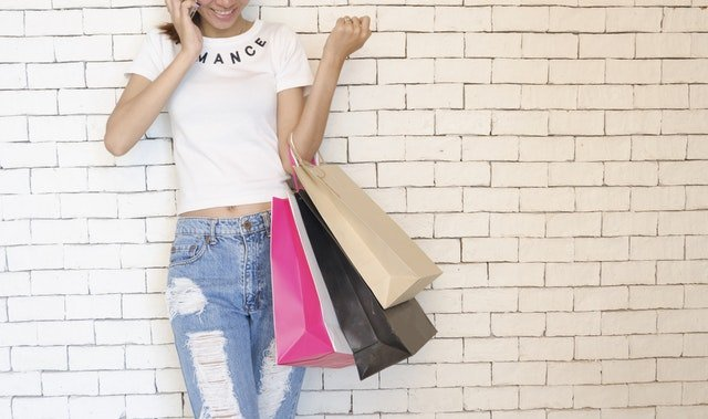 woman wearing jeans, talking on phone, holding shopping bags your home is cluttered and how to fix it