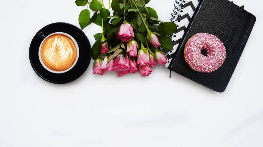 Flatlay, cup of coffee, pink tlips and a journal and donut on a white background