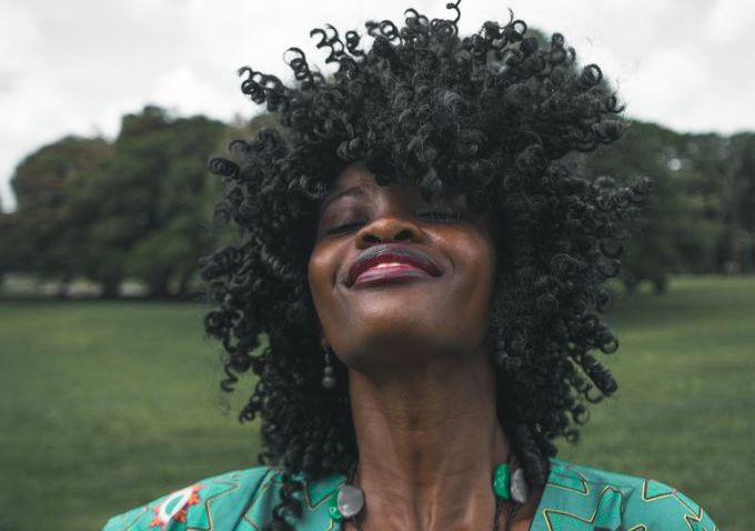 woman in green top, afro hair, looking at the sky smiling