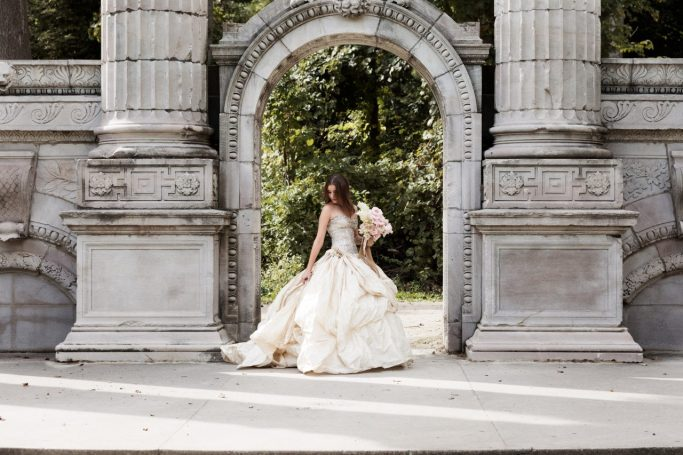 bride in wedding dress near archway