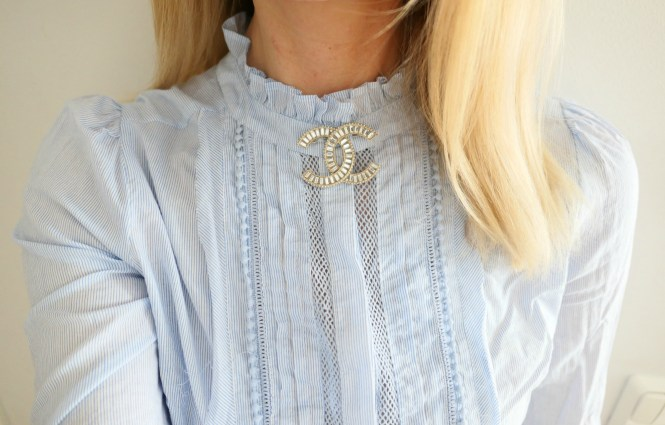 Chanel brooch and baby blue lace blouse.