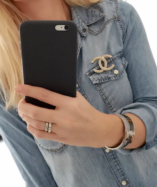 Wearing a Chanel brooch on a demin shirt with Hermes clic bracelets.