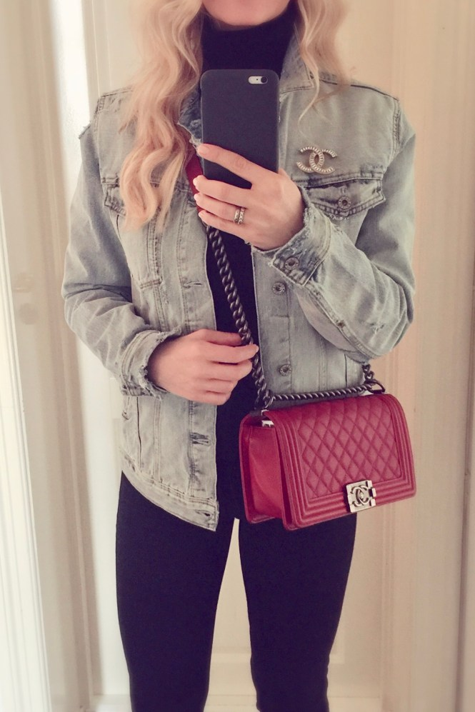 Wearing an oversized denim jacket with a Chanel brooch and red Chanel Boy bag.