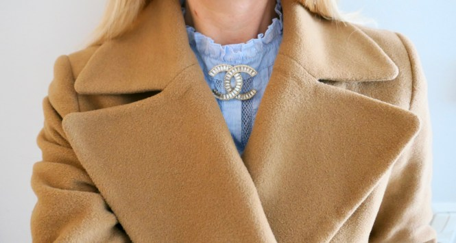 Wearing a Chanel brooch with a blue lace shirt and camel coat.