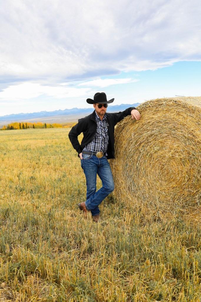 Rip Wheeler Halloween Costume Ideas: jeans, a plaid shirt, belt buckle, a black cowboy hat, cowboy boots and aviator sunglasses