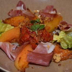 Gebakken meloen met een fondue van rode paprika en rauwe ham