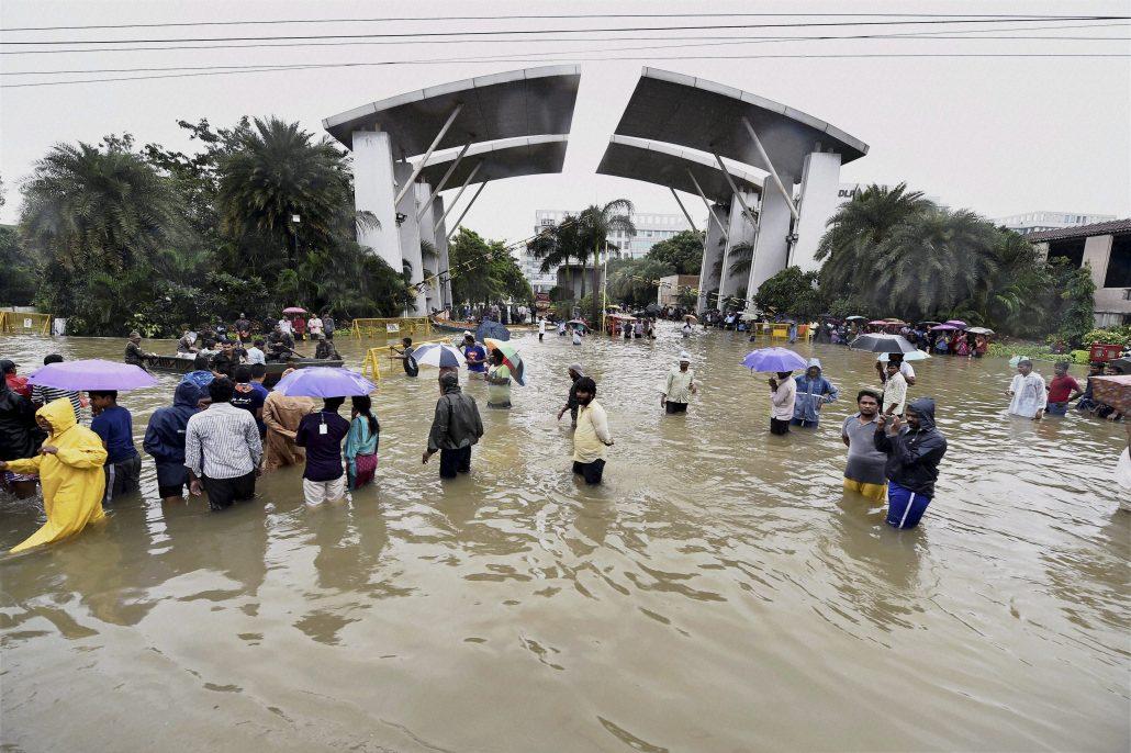 Chennai: People wade through waterlogged road following heavy rains at Porur in Chennai on Wednesday. PTI Photo (PTI12_3_2015_000031B)