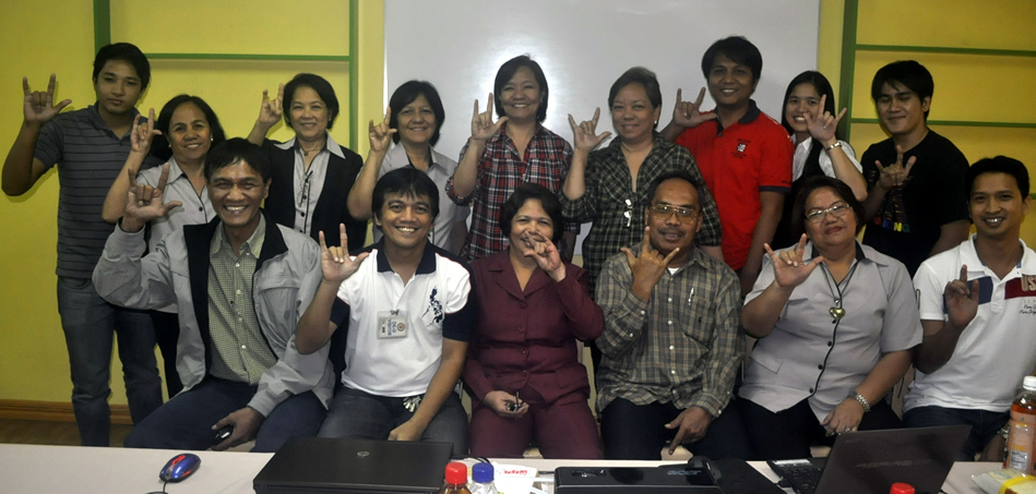 """DILG and PIA participants do the """"I Love you"""" hand sign."""
