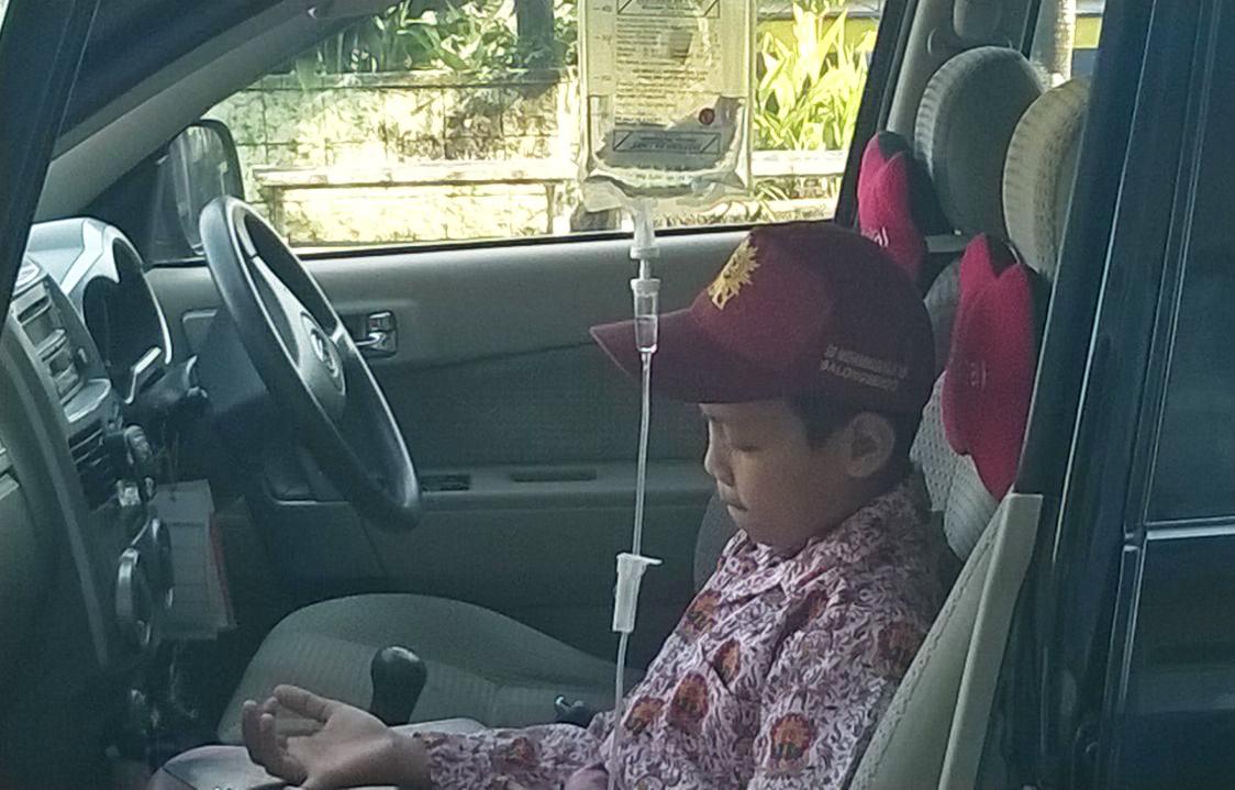Fauzan mengerjakan soal Ujian Sekolah di mobil dengan kondisi tubuh diinfus (foto dok sekolah)