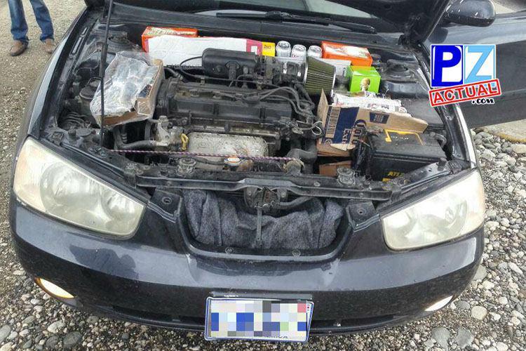 Policía decomisa botellas de licor que eran transportadas junto al motor del vehículo.