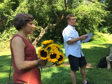 My brother John reads a eulogy. His wife Eileen holds sunflowers she brought for later