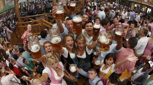 People wearing traditional Bavarian clothes toast with beer during the opening of the 177th Oktoberfest in Munich