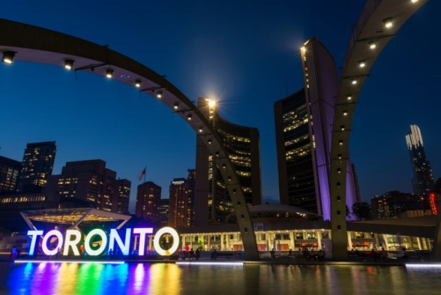 Toronto, Canada - September 6, 2015: Night long exposure of the fountain in Nathan Phillips Square with the illuminated City Hall and the Freedom Arches in the background.