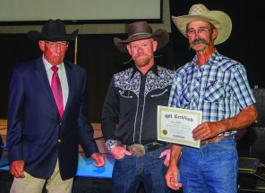 Smokey Pritchett (left) and Chaz Mitchell (center) present a custom hat certificate, donated by Chaz Mitchell Hats, to Scott Seeklander. • Photo by John O'Hara