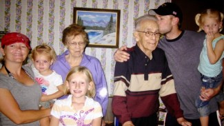 Shane Plummer standing with grandfather and family