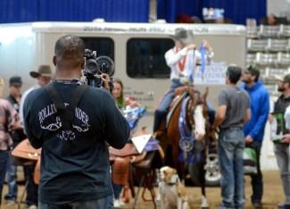 camera man filming a horse