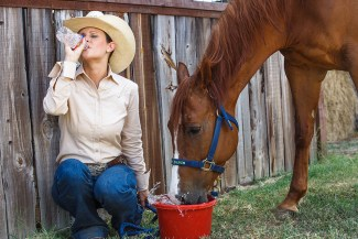 person and horse drinking water together