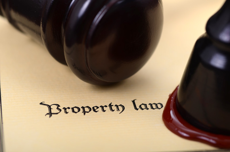 Gavel over thick paper saying property law and an official seal