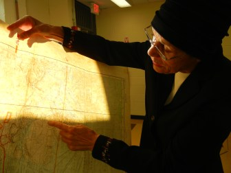 Janette James examines her father's map of the world at the St Albans Community Library in May 2014.