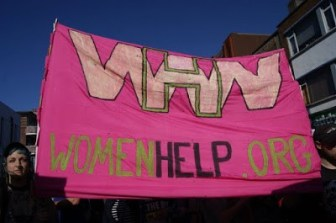 A banner from the group, Women Help Women