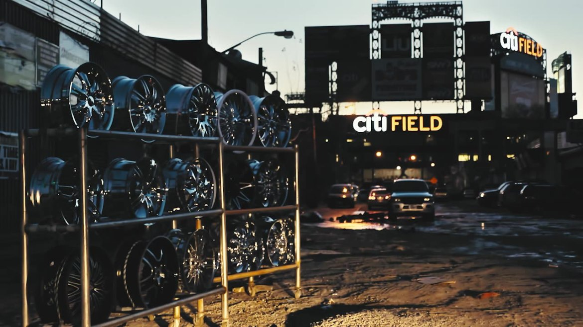 A rack of chrome rims at Willets Point Queens, with Citi Field in the background.