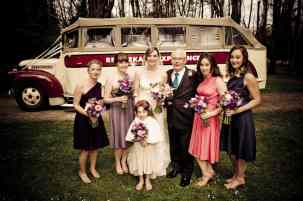 A bridal party poses for a photo in front of the Remarkable Experience vintage Chevrolet convertible buses