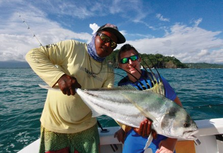 Man and boy holding roosterfish