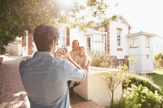 father taking a picture of family outside of house