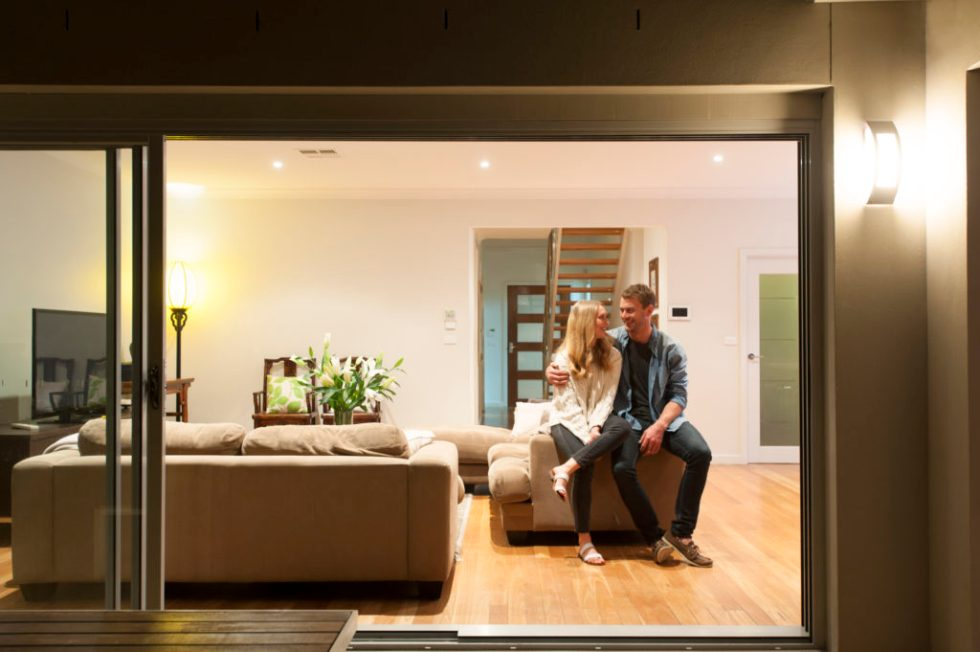 Couple relaxing in their home at night. They are both wearing casual clothes and embracing. They are looking at each other and smiling. The house is contemporary with an open plan al fresco style. Copy space