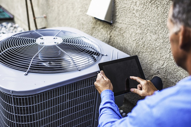 Maintenance worker inspects an air conditioning unit