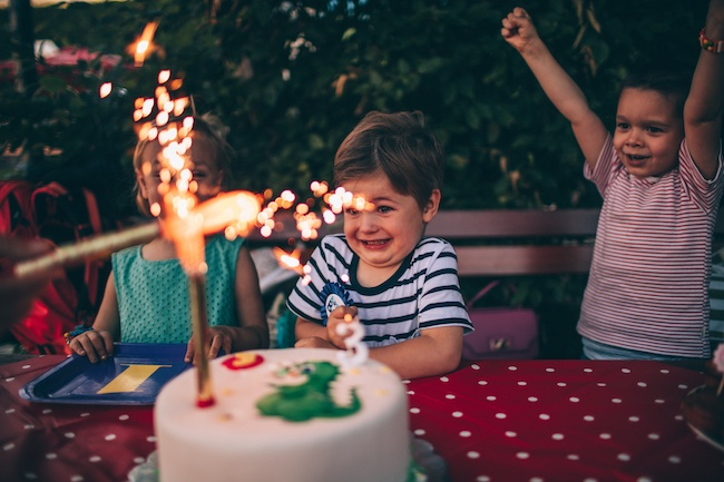 Photo of a children at a birthday party blowing out candles on a birthday cake
