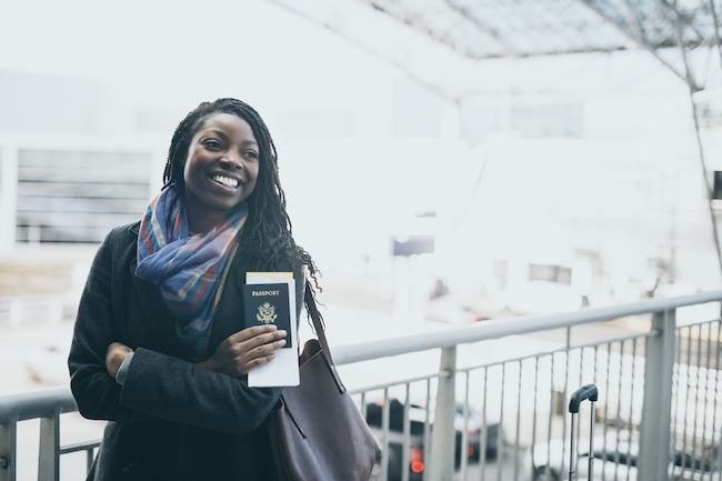 Young woman at airport holding passport