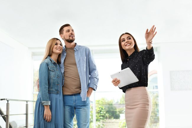Real estate agent with young couple looking at home.