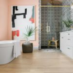 HGTV Dream Home 2020 - Bathroom featuring white tub, sink and black and white tile, peach walls
