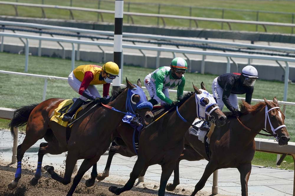 FILE - In this Friday, May 22, 2020, file photo, jockeys wearing face masks ride in the first horse race at Santa Anita in Arcadia, Calif. After a spike of horse deaths in 2019 and early 2020, Santa Anita had zero racing fatalities during its summer meet. (AP Photo/Ashley Landis, File)