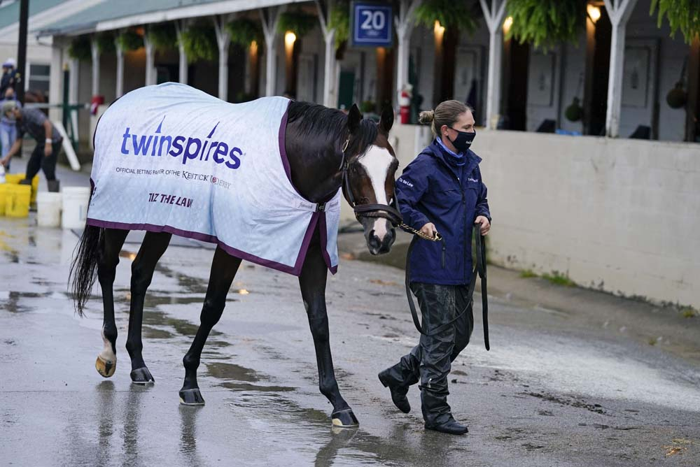 Kentucky Derby entry Tiz the Law is lead back to a stall following a bath at Churchill Downs, Thursday, Sept. 3, 2020, in Louisville, Ky. The Kentucky Derby is scheduled for Saturday, Sept. 5th. (AP Photo/Darron Cummings)