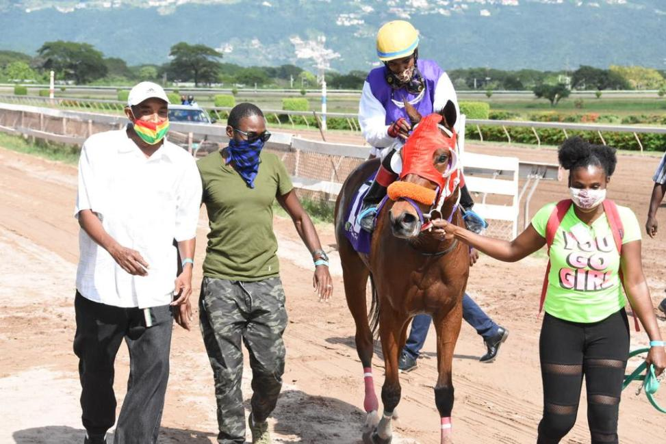 Trainer Marlon Anderson (left) leads in his winner Colawill. The jockey is Carlos Blake.