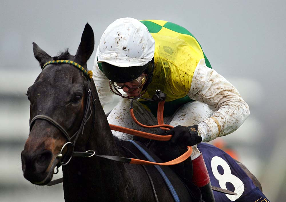 (FILES) In this file photo taken on March 16, 2005 Mick Fitzgerald riding Trabolgan rides along the home straight to win The Royal and Sun Alliance Steeple Chase, at The Cheltenham Festival. -