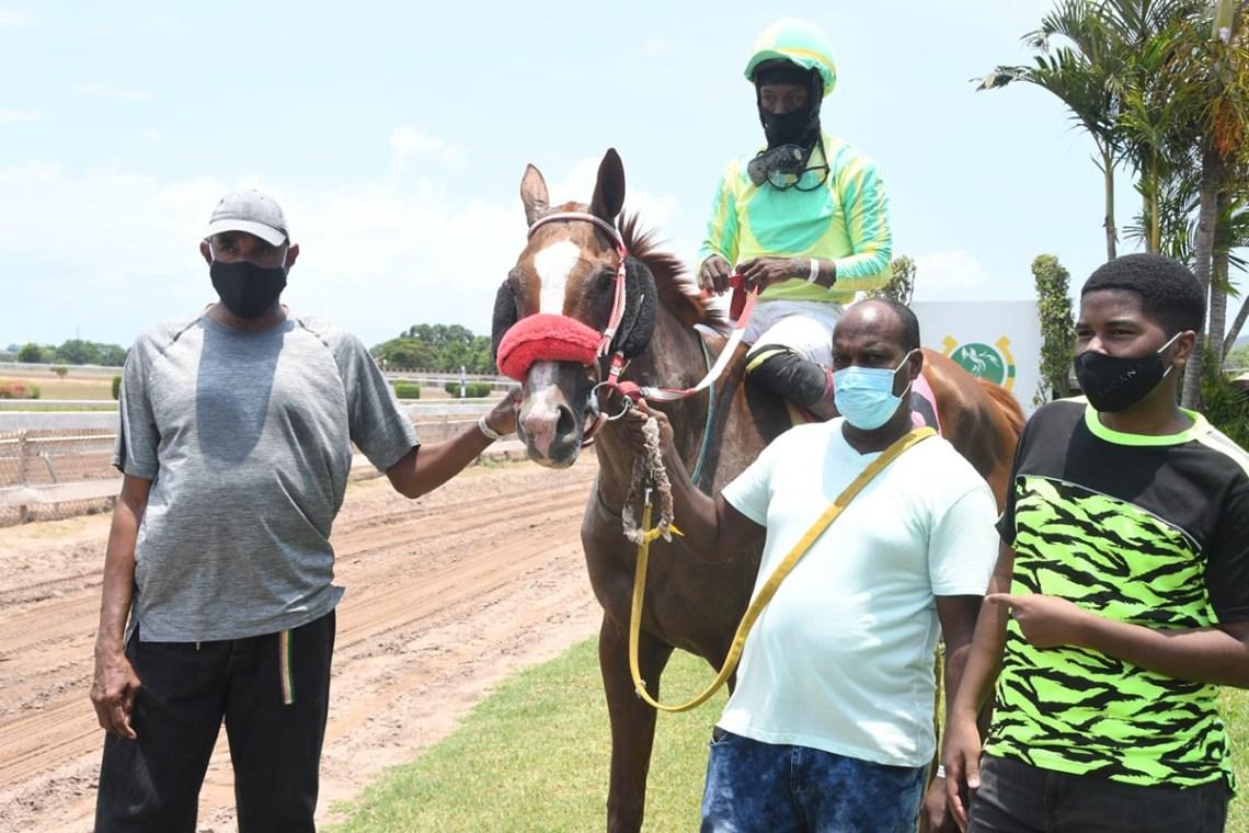 Trainer Marlon Anderson (left) with Champion Michaela. The jockey is Javaniel Patterson)