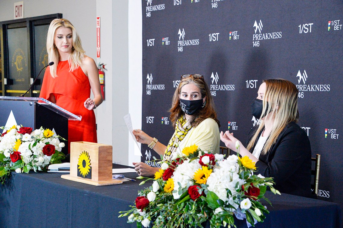 Acacia Courtney, left, Preakness horse racing host; Jillian Tullock, center, Maryland Jockey Club racing secretary; and Trish Bowman, race official, selecting post positions Tuesday, May 11, 2021, in Baltimore for Saturday's Preakness Stakes horse race.