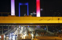 """Turkish soldiers block Istanbul's iconic Bosporus Bridge on Friday, July 15, 2016, lit in the colours of the French flag in solidarity with the victims of Thursday's attack in Nice, France. A group within Turkey's military has engaged in what appeared to be an attempted coup, the prime minister said, with military jets flying over the capital and reports of vehicles blocking two major bridges in Istanbul. Prime Minister Binali Yildirim told NTV television: """"it is correct that there was an attempt,"""" when asked if there was a coup. (AP Photo/Emrah Gurel)"""