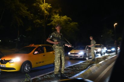 """A Turkish security officer stands on guard on the side of the road on July 15, 2016 in Istanbul, during a security shutdown of the Bosphorus Bridge. Turkish Prime Minister Binali Yildirim on July 15 denounced what he said was an """"illegal attempt"""" by elements in the military after bridges were partially shut down in Istanbul and jets flew low over Ankara. """"We are working on the possibility of an attempt. We will not allow this attempt,"""" he told NTV television by telephone, without expanding on the nature of the move but saying it was by a group in the Turkish military. / AFP / BULENT KILIC (Photo credit should read BULENT KILIC/AFP/Getty Images)"""