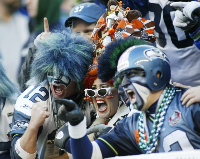 Seattle Seahawks fans surround a Cleveland Browns fan as she mugs for TV cameras Sunday, Nov. 30, 2003 at Seahawks Stadium in Seattle. (AP Photo/Ted S. Warren)