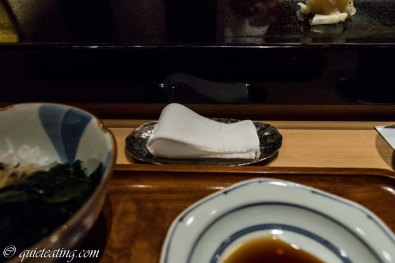 A wet towel to clean your fingers. Sushi is best eaten directly with your hands