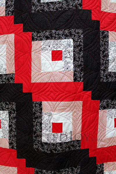 Imogene's Log Cabin is a beautiful example of a classic log cabin in black and red. She cleverly chose fabrics that allowed for the gradient darkening of the two halves while not adding additional colors outside the three main colors of red, black, and white.