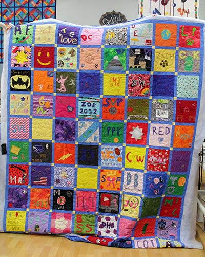 Hand embroidered blocks on a memorial quilt for a school